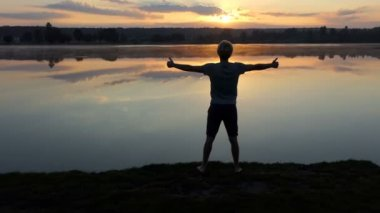 Cheery man keeps two thumb up gestures at sunset in slo-mo