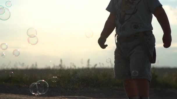 Cute Little boy and soap bubbles at sunset in slow motion