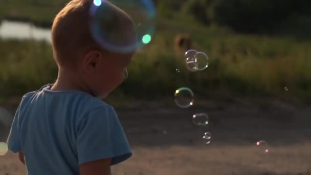 Funny Little boy and soap bubbles at sunset in slow motion. Boy in blue t-shirt.