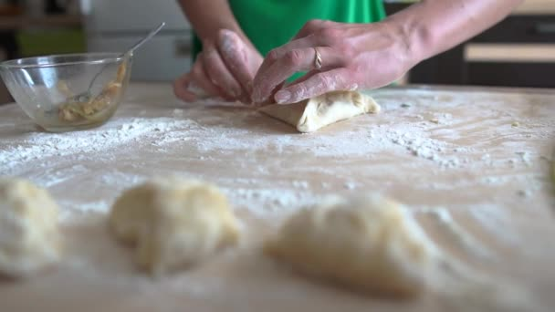 Cooks hands hands make a triangle-shaped pie from the dough, slow motion.