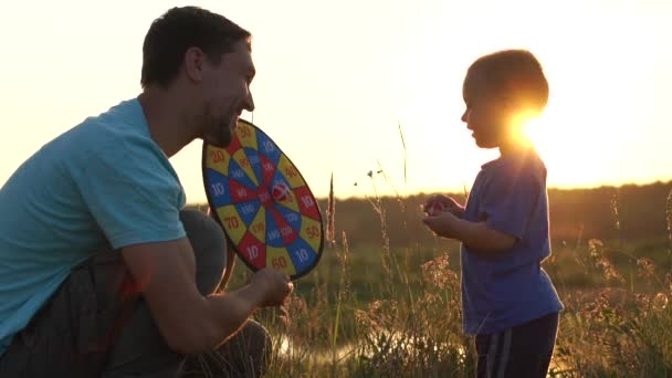 Dad plays with his son at sunset, the baby misses the ball.