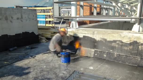 Roofer Installing Roofing Felt With Heating And Melting Of Bitumen Roll By  Torch On Flame During
