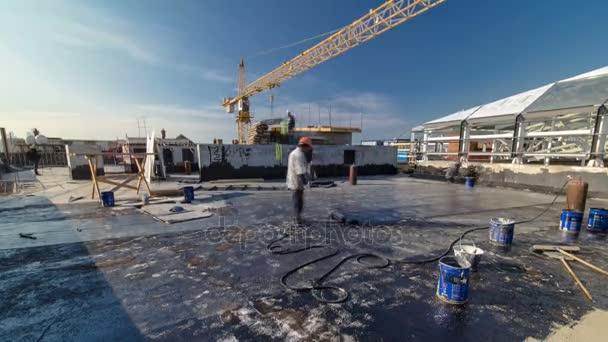 Pokrývač, instalace zastřešení cítil s topení a tání asfaltu roll autogenem na plamen během timelapse opravy střechy