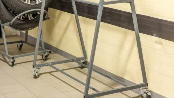 Auto mechanik dal pneumatiky z vozíku do stojanu v automatické opravy služby timelapse