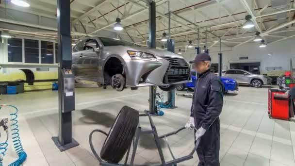 Auto mechanik šroubování a odšroubování kola automobilu zdvižené automobilu na opravit čerpací stanice timelapse hyperlapse