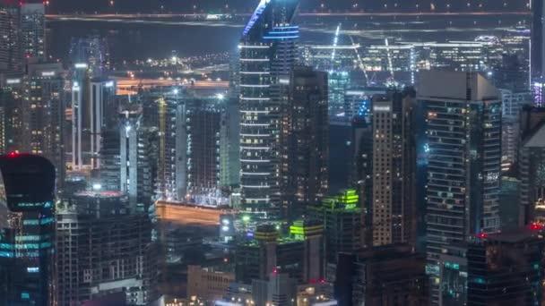 Panoramatický pohled na věže obchodních prostor v Dubaji noci.