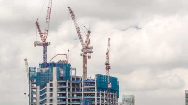 Working crane on a modern office building under construction against cloudy sky in Singapore timelapse.