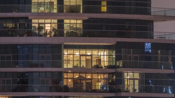 Řady zářících oken s lidmi v činžovním domě v noci.