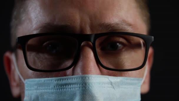 Nahaufnahme eines Mannes mit Brille und medizinischer Maske vor schwarzem Hintergrund. Oberflächlicher Fokus.