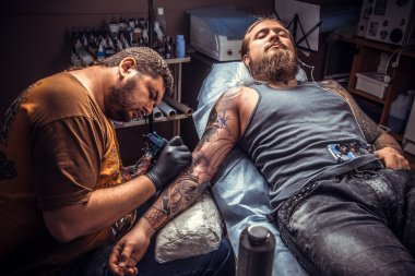 Tattooer showing process of making a tattoo in tattoo studio