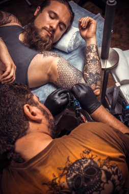 Professional tattooer making a tattoo in studio