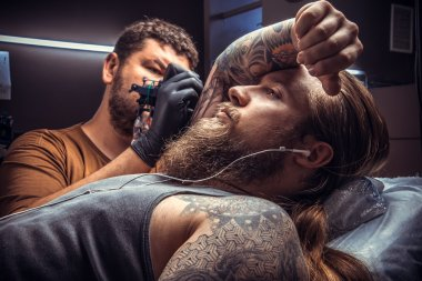 Professional tattooer create tattoo in studio