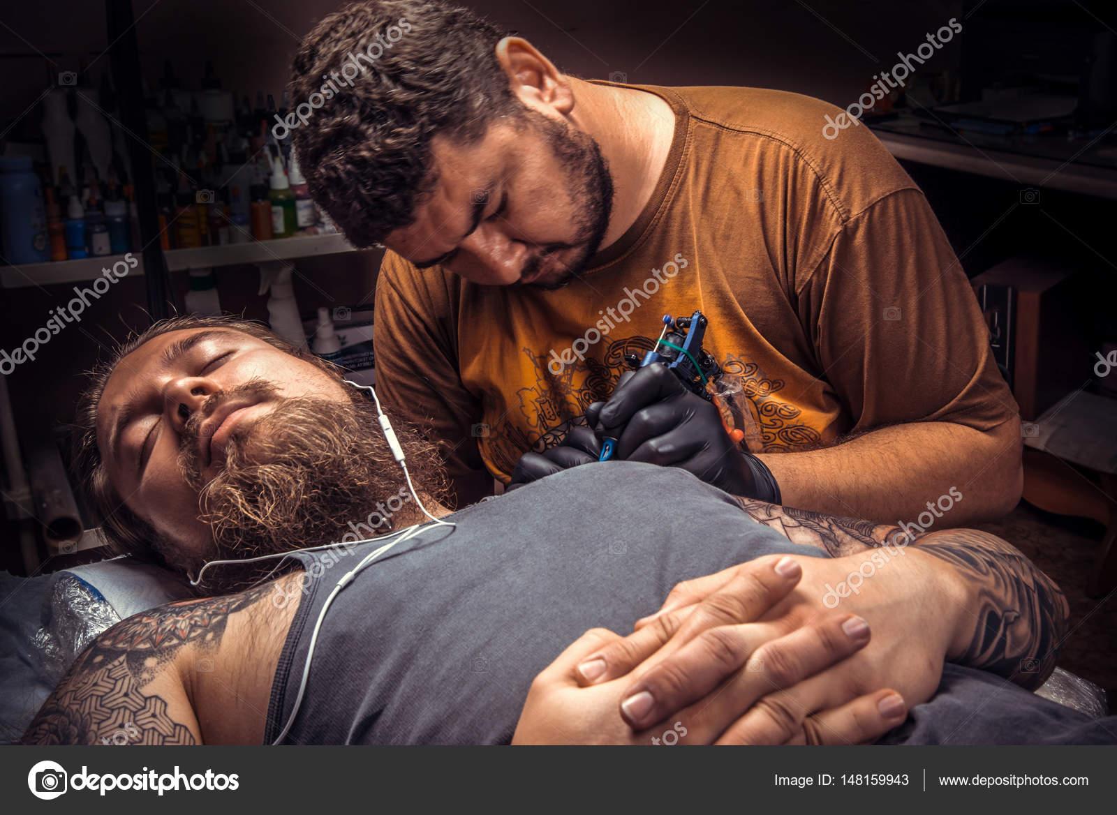 79a3a2f55 Professional tattoo artist making a tattoo in tattoo parlour./Master works  in tattoo studio. — Photo by Mr.Prof