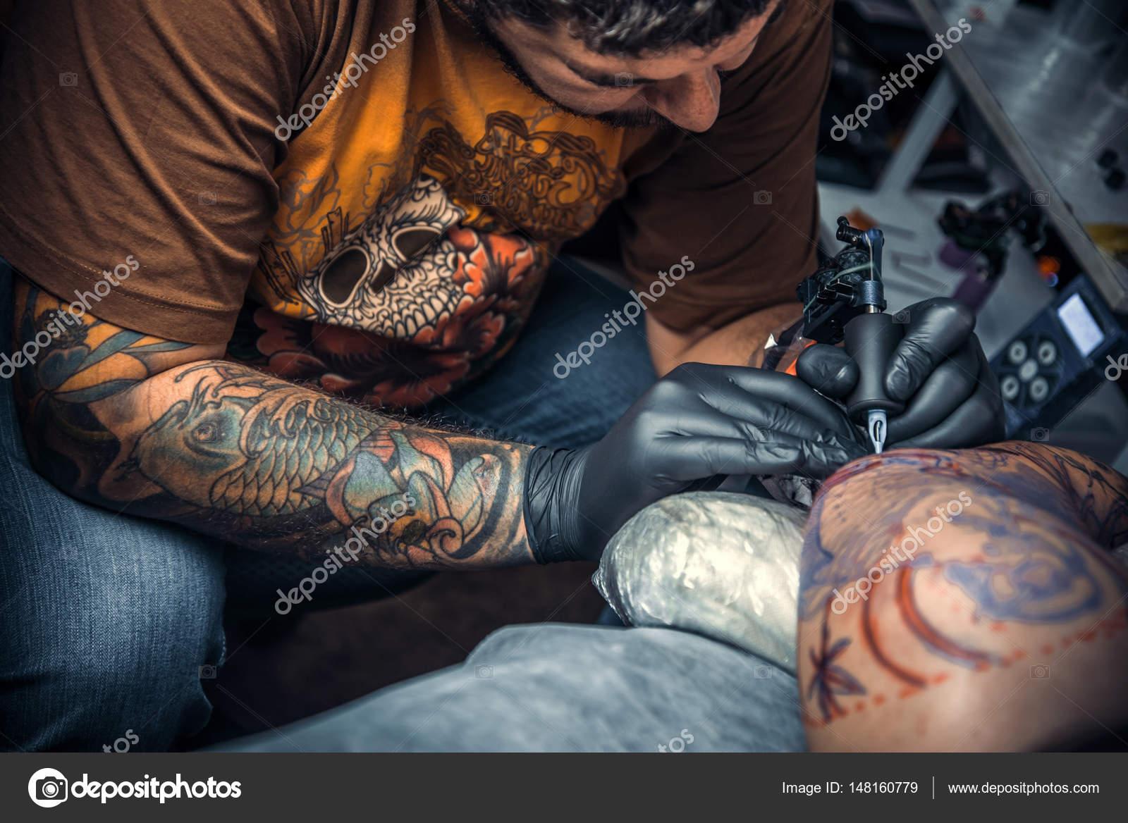 9dc433de5 Professional tattoo artist works in tatoo salon./Master doing tattoo in tattoo  studio.