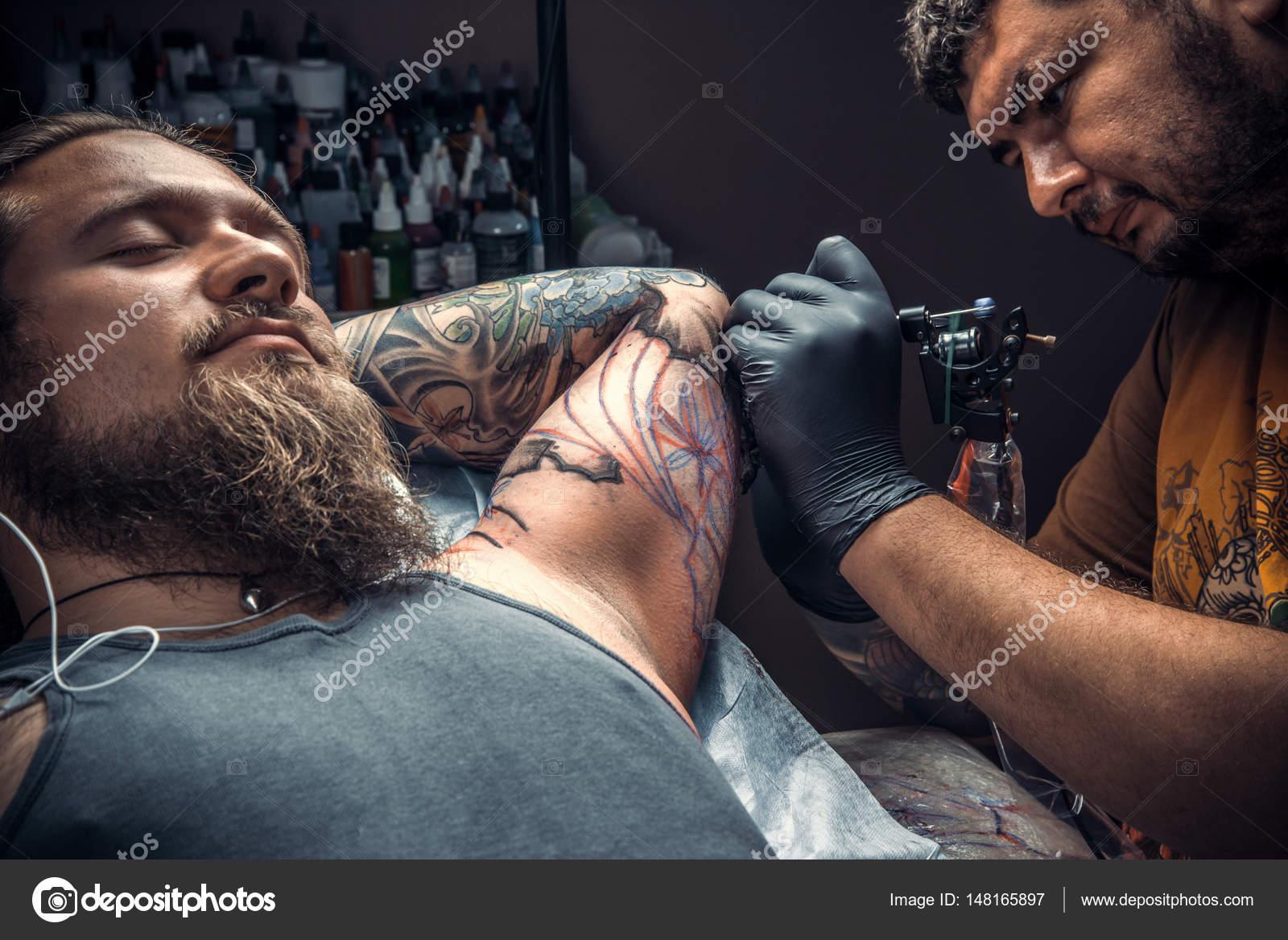 49843872f Tattoo master create tattoo in tattoo parlour./Professional tattoo artist  makes cool tattoo in tattoo studio.