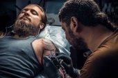 Fotografia Tatuatore lavora in studio di tattoo. / tatuatore professionale facendo un tatuaggio nello studio tattoo