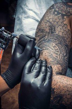 Tattoo specialist doing tattoo in tattoo studio