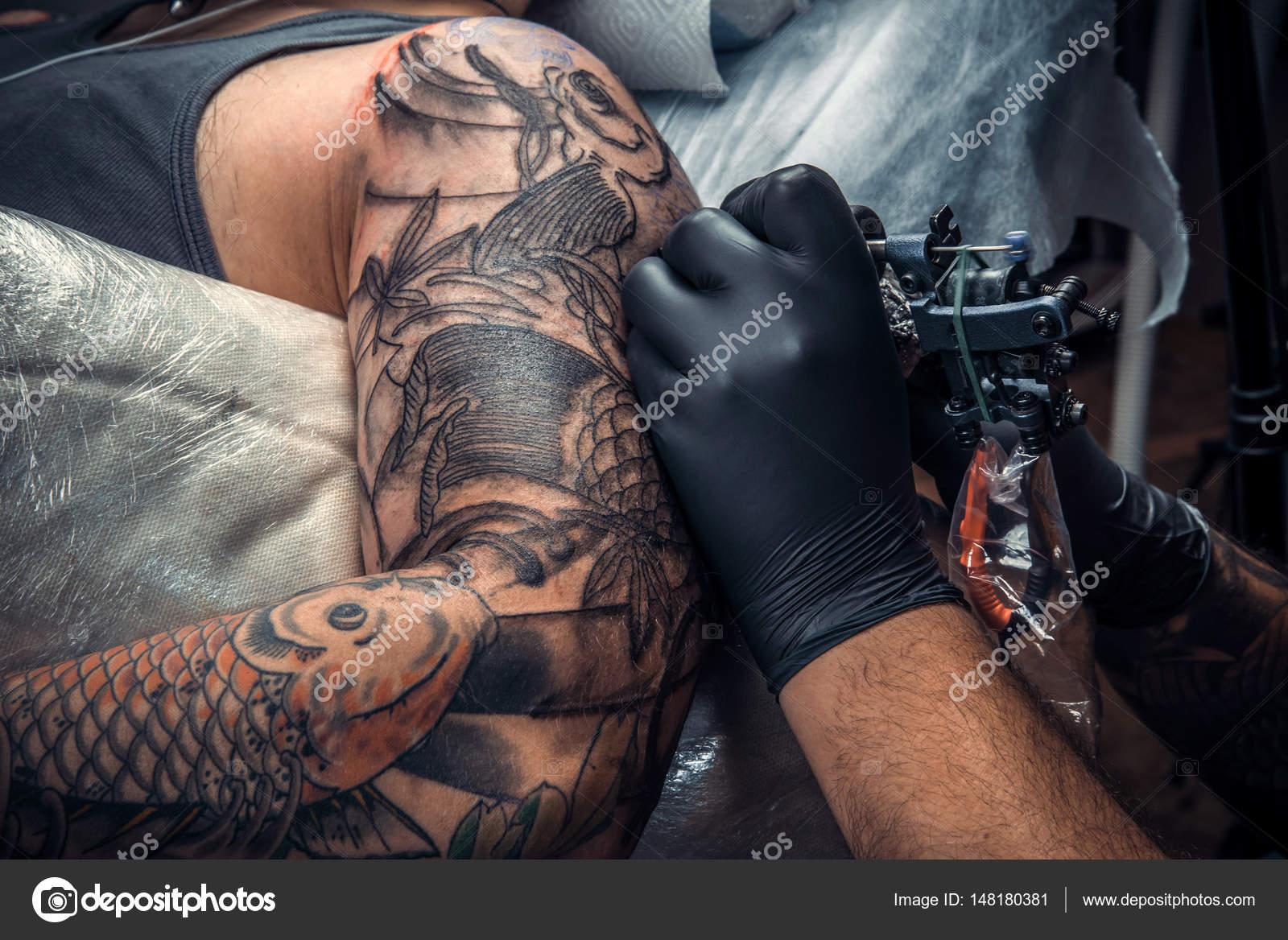 a40e178c2 Professional tattoo artist makes cool tattoo in tattoo studio — Stock Photo