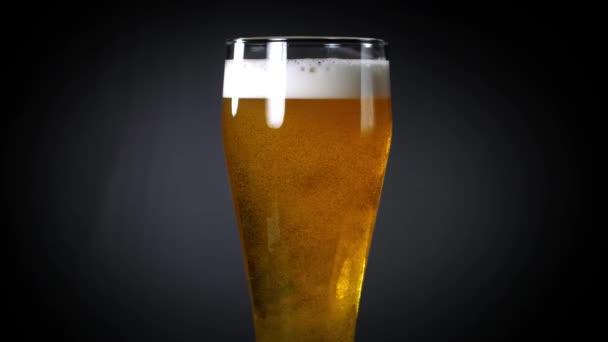 Üvegbe öntött sör egy feketén. Sör egy söröspohárban buborékokkal