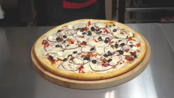 Kuchař krájí připravenou pizzu