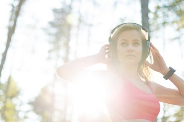 Young attractive sportswoman listening to music wearing headphones. Sport, fitness, workout concept