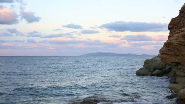 Mořské vlny zřítilo do skal při západu slunce