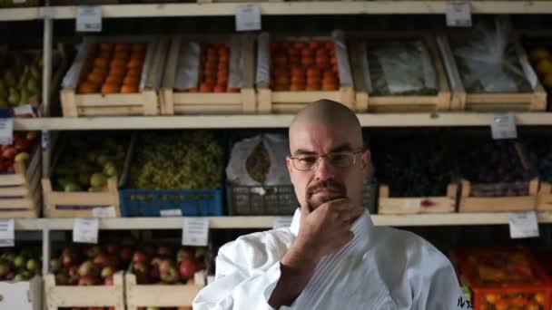 Muž na pozadí s regály s ovocem a zeleninou