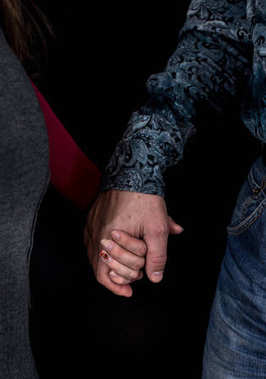 Man and woman holding each other's hands.Closeup on black background.Love and care concept.