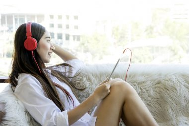 Girl sit relax on her sofa listen to music on headphone