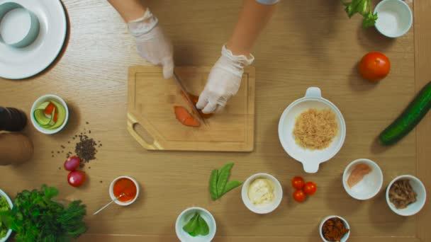 Vista superiore della mano femminile tagliata il pesce, pomodoro, cetriolo, formaggio, salsa, origano