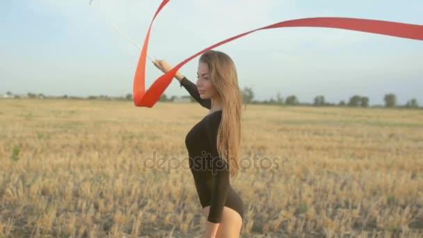 Fiatal barna nő tánc ritmikus gimnasztika, modern, piros szalaggal.