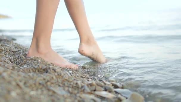 Žena na pláži naboso. Dívka chůze v mělké vodě při západu slunce a užívání si přírody.