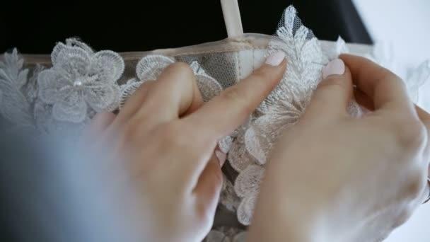 Módní návrhářka pro nevěsty v jejím ateliéru piny krajky jehly a květiny Wdding šaty. Zajistit s obrysem špendlíky a jehly