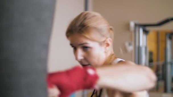 Formazione di giovane donna con un sacchetto di perforazione in un Club di boxe