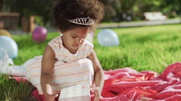 Šťastný malý afroameričan dívka hrát s dárek box na její narozeniny