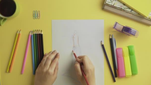 Horní pohled módní návrhářka použít barevné tužky na kreslení šaty skica