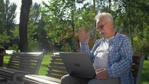 Wütender älterer Mann spricht per Skype, sitzt auf der Bank im Garten. Ein Rentner hält einen Laptop auf seinem Schoß. Er wedelt mit der Hand, schimpft auf jemanden
