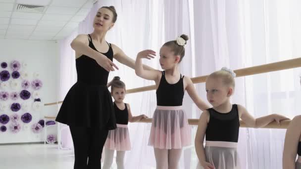 Teachers show how to dance to little ballerinas. Girl dancer in ballet school learns to dance. Young ballerinas jumping in training. School of ballet.