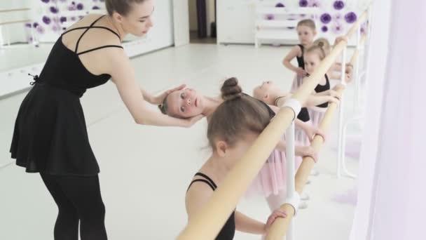 Holčičky tančí balet. Děti v baletní třídě. Malé baletky a učitelka. Krásný výhled.