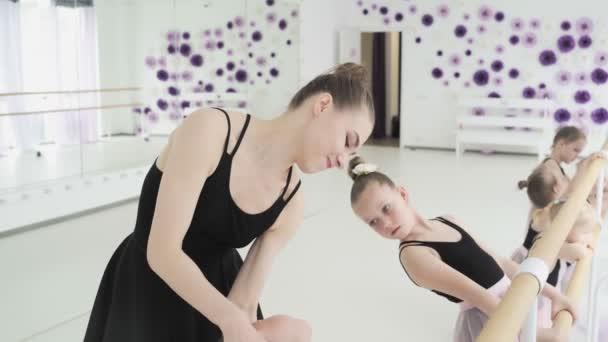Skupina malých baletních tanečnic v růžových trikotech a sukních visících na baletní tyči a cvičících v tanečním studiu