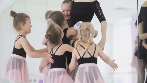 Cute Female ballet teacher and her little students are hugging