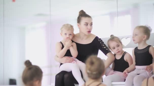 Mladý učitel baletu sedí na lavičce v baletní škole s malými dívkami v černém trikotu a komunikuje s nimi