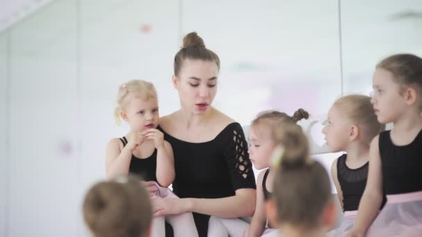 Young ballet teacher sitting on bench in ballet school with little girls in black leotards and communicating with them