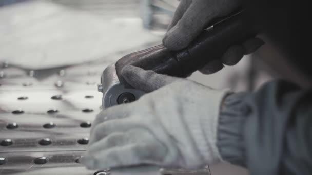 Pracovník ruce v rukavicích řezání kovové trubky