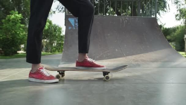 Skateboarder steht mit Skateboard und schiebt es weg