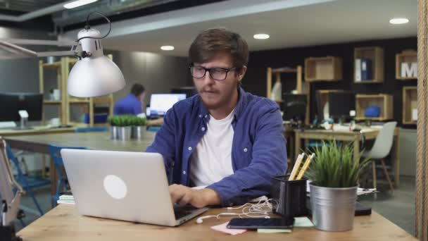 Creative man with glasses working in the office at the computer