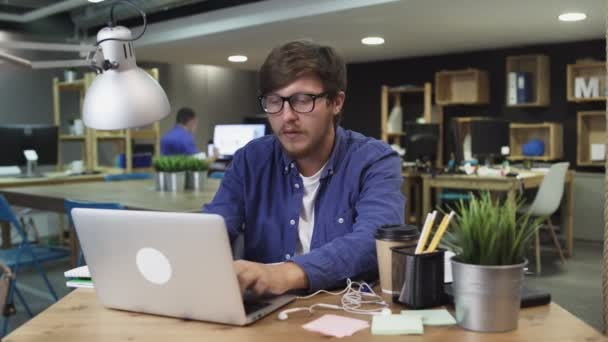 Creative man with glasses is drinking a coffee while working in the office at the computer