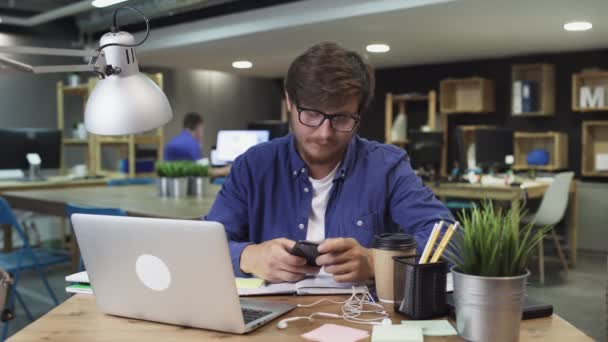 Businessman Sitting at His Desk Works on Desktop Computer in the Stylish Office, Picks up and Starts Using Smartphone, Uses Social Media App, Emailing Business Partners, Messaging.