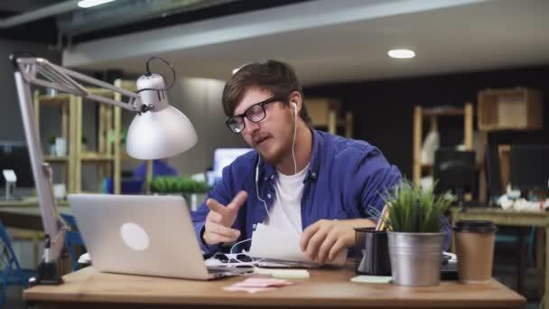 Lustiger Mann mit Kopfhörer spricht mit Kollege per Webcam und überprüft Dokumente