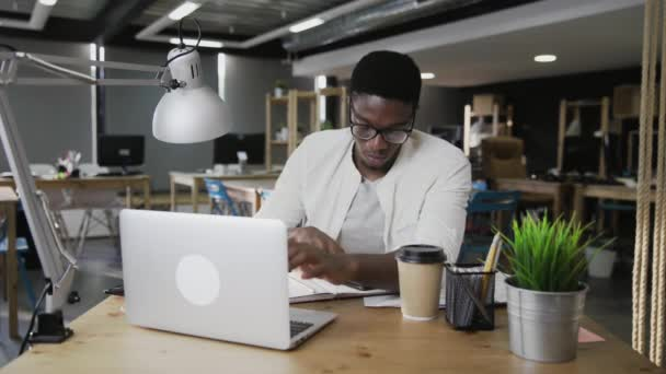 African businessman is working on laptop and answering calling in modern office